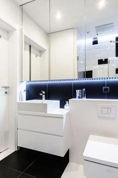 Wisząca szafka nad umywalką łączy dwa w jednym – mebel do przechowywania i lustro. Umieszczona pod nią listwa LED tworzy dekoracyjną poświatę na czarnych kaflach. Prosta biała szafka podumywalkowa została wpasowana we wnękę przy gzymsie ukrywającym podtynkowy system spłukujący.