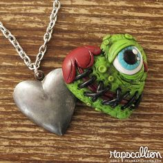 Behind a layer of haphazardly stitched slimy green skin and one big creepy eyeball lies a place to store your precious photos or a tiny treasure.  Perfect for the zombie lover in your life!  - Hand sculpted from polymer clay - Hand painted detailing - Glazed for a nice shine - Antique silv...