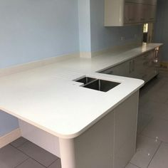Installed We fitted the Bianco De Lusso white quartz to this high gloss grey kitchen in Bishops Stortford. We love the two long runs of worktop and the separation onto open-plan living with the sink area and breakfast bar. Open Plan Living, How To Run Longer, Corner Desk, Kitchen, Furniture, Home Decor, Corner Table, Cooking, Decoration Home