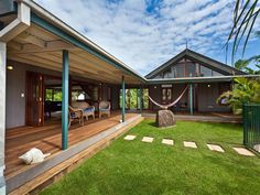 The L-shaped home makes a perfect beach home either in the suburbs or by the sea. Love love love wrap around patio deck
