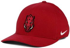 Use this Nike NCAA Classic Swoosh cap to show your support for the Arkansas Razorbacks, be it for their academia or the sports teams they field. Great for daily wear, this cap is comfortable and stylish all year long. Mid crown Structured fit Normal bill Embroidered team logo at front Stitched Nike swoosh logo at left side Embroidered team logo at back Stretch fitted Rayon/nylon/cotton/polyester Spot clean only
