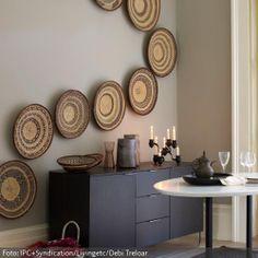 Durch die Wandteller aus Bast im Ethno-Look erhält der Freiraum über dem Lowboard einen außergewöhnlichen Look. Mehr Inspiration zu Wanddekoration auf www.roomido.com/wohnen-einrichten/ideen/wanddeko