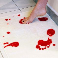 Bloody Carpets     Before beginning this DYI, make sure to use a surface (old rugs/shower carpets, etc.) that you don't mind getting paint on. Next, pour some red paint onto a paper plate and dip your feet in. Once your feet are lathered up, walk on whatever surface you are using and watch your crime scene bloody prints come to life. Credit: Shenanigans & Tomfoolery