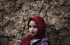 An Afghan refugee girl, leans on a wall while talking to her friends, unseen, in an alley of a poor neighborhood of Rawalpindi, Pakistan.