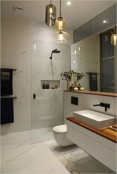 28 Bathroom Lighting Ideas to Brighten Your Style White marble wall tiles in bathroom / wood shelf and wood bench in bathroom / glass pendant lights in bathroom / Laufen basin Bathroom Pendant Lighting, Modern Bathroom Lighting, Modern Bathroom Design, Contemporary Bathrooms, Pendant Lights, Modern Lighting, Bathroom Designs, Vanity Lighting, Contemporary Apartment