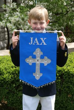 This is my Pinterest board & this my son Jax w/ the First Communion Banner I made for him w/ ideas I pinned on the board. - I used blue satin fabric w/ stiff interfacing, sewed in beaded fringe & glitter ribbon to hang from the rod. Rhinestone letters were purchased from Michael's. Cross is iron on glitter fabric cut into a shape of a cross. Stick-on gems on the cross. Rod has metallic rope & tassels. Jax was very proud of his banner. Post if you do something similar - I would love to see…