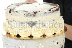 """När du lagt ihop din tårta, gör ett vad vi kallar """"crumbcoat"""". Täck tårtan med ett tunt lager smörkräm eller annan frosting. På det sättet slätas kanterna ut och du får en jämn och fin grund på din tårta att arbeta med. Efter det, går dekoreringen som en dans! Vill du veta mer om hur du täcker en tårta? Boka ett homeparty med inriktning """"Tårta"""" på info@sugarkitchen.se, så visar vår närmsta konsulent dig! www.sugarkitchen.se"""