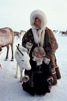 A Tundra Nenets woman with her daughter and a pet reindeer calf. Gydan Peninsula, Yamal, Western iberia, Russia.