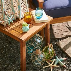 Nautical or sea-themed décor like this navy patio furniture set and sea shell wind chimes, seahorses, anchor, light houses, starfish, and lifesaver accents make for the perfect pool-side or backyard oasis.