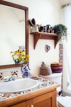 paredes pintadas de branco; moldura de madeira no espelho; cuba branca; azulejos coloridos; vasinho de porcelana; flores amarelas; prateleira de madeira; plantinha;
