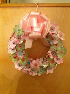 Made from punched out paper flowers and circles; held together with plain brads and colored using a sharpie and a dollar tree foam wreath :)