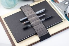 [jour.nal ban.do.lier n.] a strap fitted with small loops for carrying pens, pencils, and other handy tools wrapped around a journal, planner, or