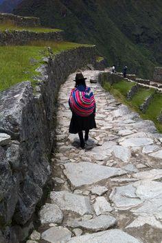 A Quechuan woman walks seemingly alone through Macchu Piccu