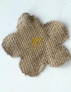 Een bloemetje van jute. Het jute is afkomstig van hergebruikte koffiezakken. De randen zijn gestikt om rafelen verder te voorkomen.