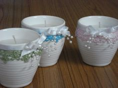 Hand poured, scented candles in ceramic containers decorated with blue / green / pink coloured lace, pearls and white ribbons