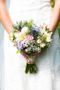 Wild Flower bridal bouquet wrapped with hessian and lace - Image by Julie Warner Photography - Wendy Makin Lace Wedding Dress & flower crown for a rustic wedding in a barn with pastel DIY decor, mis-match bridesmaids gowns and groomsmen in bow ties.