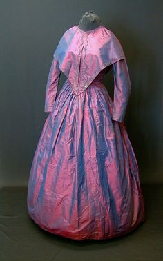 This 1840s dress and matching pelerine is an example of a very creative way to fake purple for a dress. The fabric used for this dress is a red/blue changeable silk, that is red threads on the warp and blue on the weft, or visa versa. The resulting fabric looks red from some angles, blue from others, but is generally perceived as purple.