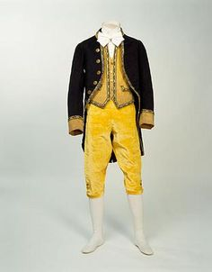 Distinctive livery was a feature of male servant's dress in aristocratic households for two centuires from the Restoration of Charles ll in 1660. This livery outift with its bold yellow colouring for the breeches and waistcoat, dates from the middle of the nineteenth century and still shows features of eighteenth century dress including the style of the coat, and the breeches.