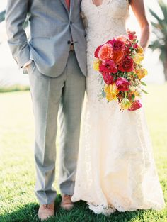 This teardrop shaped bridal bouquet featured garden roses, spray roses & tulips in fuchsia, coral & yellow with textured greens for this boho beach wedding. | Bob Gail Events #bridalbouquet #beachwedding