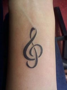 Treble clef tattoo. I like how it breaks up, but flows at the same time.  Just needs a star on each side.