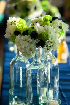 Add sand to the bottom. Wine bottle with flowers and pearls.