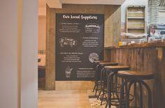 Pom's Kitchen & Deli - Open kitchen, industrial stools, blackboard