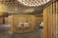 Tang Palace Restaurant is Wrapped in a Geometric Bamboo Skin | Beijing-based design firm FCJC used a limited pallet of bamboo to transform an ordinary space into a stunning contemporary restaurant. The interior of the Tang Palace is enclosed by a flowing grid of bamboo strands that bring the 9 meter-tall room down to human scale and conceal the private dining rooms hung above.
