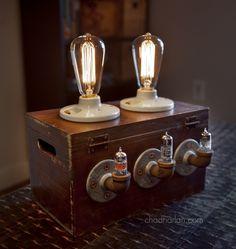 Industrial retro, steam punk machine age Edison lamp. Ceramic sockets, antique box, iron pipe fittings, and vintage vacuum tubes.