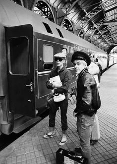 David Bowie and Iggy Pop at the Berlin railway station.  Bowie and Iggy go together like bacon and eggs.  If it's Berlin, this must be from the '70's.