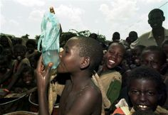 A Somali child drinks water from a plastic bag while waiting for food distribution in a Baidoa refugee camp December 14, 1992. REUTERS-Yannis Behrakis