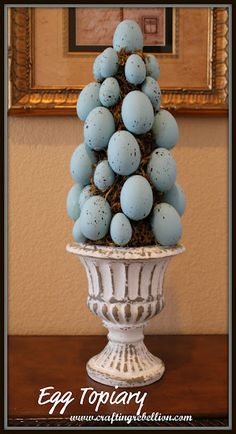Williams and Sonoma - simple enough to do on your own: urn of choice, triangle florist foam, Spanish moss hot glued and blue speckled eggs hot glued on the moss.