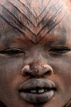Africa | a close up of a Mundari girl in a cattle camp near Tarakeka; her face has been covered with ocher and ash. On her forehead are some tribal scarification marks. Southern Sudan | © Bruno Zanzottera.