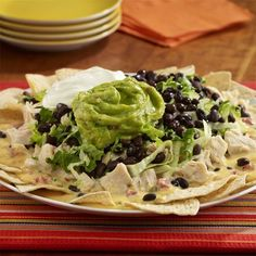 Loaded nacho recipe tops tortilla chips with queso dip, lettuce, chicken and black beans for hearty fare.  Velveeta is a product of Kraft Foods Inc.