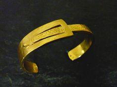 Ce bracelet manchette fabriqué en étain est disponible en argenté et en doré. La partie la plus fine est brillante, la plus large est mat afin de