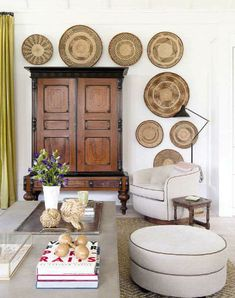 classic with rustic inspired living , vintage wardrobe, woven baskets on the wall, mustard curtains, white walls, round taupe foot stool