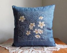 Decorative embroidered denim pillow, sashiko design, flowers on branch in swirling background of clouds or waves