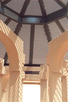 Pierced metal shade structure roof in public park; Riyadh, Saudi Arabia.