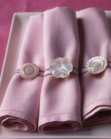 Call on loose or mismatched buttons to serve as the charming clasps on handmade napkin rings. You'll need shank buttons, which have holes on the back. We used a variety of mother-of-pearl buttons, each about 1 1/2 inches across. Thread a 12-inch length of cording through each shank, and tie its ends in a knot. Secure knot to shank with a needle and thread so that it will stay hidden behind the button. Wrap cording around a folded napkin, looping it back over the button to secure.