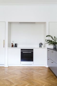 White, small and simple kitchen - the small niche previously housed built-in cabinets. They are removed and instead the niche is for the features you want to have saved a little away: cooker hood, oven and hob.
