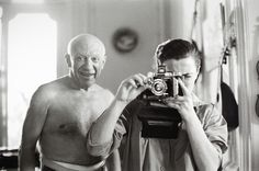Picasso looks over Jacqueline's shoulder as she aims her camera at the photographer  1957