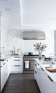 Herringbone tile backsplash, white cabinets with black pulls | Erin McLaughlin's kitchen makeover via Style at Home