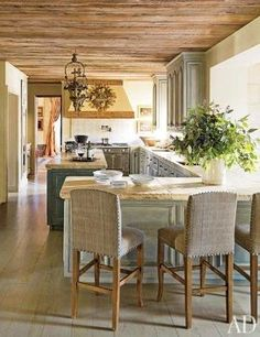 The kitchen features a La Cornue range, counters made of reclaimed 18th-century stone from Chateau Domingue, and vintage barstools | archdigest.com by janis
