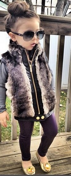 glamorous and fabulous - furry vest, leggings, flats, high bun, and big shades.