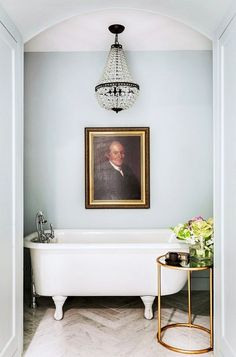 Serne blue bathtub corner with crystal chandelier and portrait.
