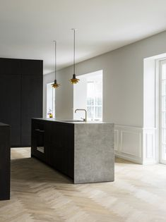 he minimalist kitchen in smoked oak with bronzed brass handles was designed by Norm Architects for the Danish kitchen manufacturer Reform, and is complemented by a sculptural kitchen island in a light gray ceramic stone, as well as a herringbone floor.