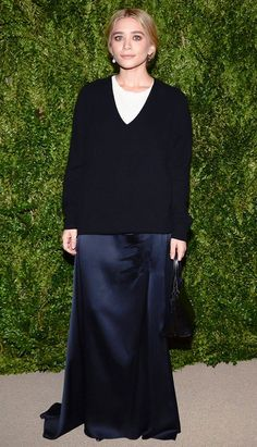 Ashley Olsen wears an oversized black sweater with an Acne Studios skirt and pearl earrings.