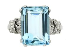 Aquamarine and diamond ring, circa 1930. A platinum ring set with one central rectangular emerald cut aquamarine in a claw setting with an approximate weight of 6.00 carats, flanked by fancy raised openwork shoulders set with eighteen round eight cut diamonds in bead settings nice-shiny-things
