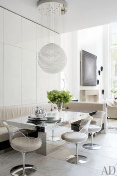 In a New York townhouse, modern lucite chairs accent a mirrored dining table and a Tom Dixon pendant light.