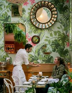 A server chats with a diner at Leo's Oyster Bar in S.F., which sports tropical wallpaper and playful touches. Photo: John Storey, Special To The Chronicle