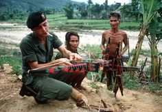 A soldier of the U.S. Special Forces is seen making friends with the Montanards in the Central Highlands of Vietnam during the war. October 1970. Photographed by Terry Fincher ~ Vietnam War